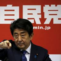 Prime Minister Shinzo Abe points to a reporter during a news conference after he was re-elected as the party leader at the party headquarters Wednesday.  | REUTERS
