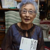 Michiko Hattori, 86, poses with her book 'Anohi Pikadon ga' ('On the Day of the Atomic Bombing') at her home in Warabi, Saitama Prefecture, in July. | KYODO