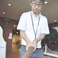A staffer at the Hoppo Kinenkan local history museum in Wakkanai, Hokkaido, shows heavy sections of cable recovered from the seabed and donated by an NTT Corp. subsidiary. | KYODO