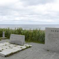 A statue stands at a former landing point of undersea telecommunications cables in Sarufutsu, Hokkaido, in July. The cables were laid from the village to the island of Karafuto, Russia's present-day Sakhalin. | KYODO