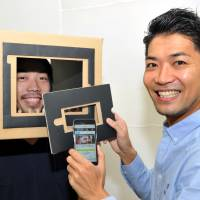 Lucy Alter Design Creative Directors Mikito Tanimoto (left) and Satoshi Aoyagi display their Solo Theater box with a smartphone at the company's office in Tokyo's Shibuya Ward. | YOSHIAKI MIURA