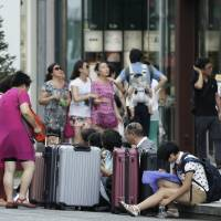 Chinese tourists sit with newly purchased suitcases in Tokyo's Ginza district in August. | BLOOMBERG