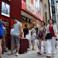 Chinese tourists exit from the home appliance retailer Laox Co.'s outlet in the Ginza district of Tokyo with shopping bags and suitcases on Friday. A favorable exchange rate and relaxed visa rules are luring many Chinese to Japan. | SATOKO KAWASAKI
