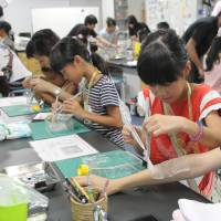 Children and parents participate in mock transplant operations using tissues as skin in a workshop organized by Japan Tissue Engineering Co. at the Gamagori Museum of Earth, Life and the Sea in Gamagori, Aichi Prefecture, in August. | CHUNICHI SHIMBUN