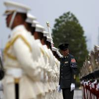 Members of a Self-Defense Force honor guard prepare for a ceremony for U.S. Air Force Lt. Gen. John Dolan at the Defense Ministry in Tokyo in June. | REUTERS