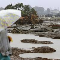 A man watches Self-Defense Forces troops and volunteers repair a breached levee on the Kinugawa River in Joso, Ibaraki Prefecture, on Wednesday. | KYODO