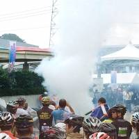 Smoke rises from a drone after it crashed and burst into flames near the starting point of the 5th Maebashi Mt. Akagi Hill Climb bicycle race in Maebashi, Gunma Prefecture, on Sunday morning. | KYODO