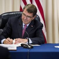 U.S. Secretary of Defense Ashton Carter and Foreign Minister Fumio Kishida sign a treaty at the Pentagon in Washington, D.C. on Monday. The pact will allow Japanese officials to enter U.S. military bases in Japan to conduct environment surveys. | AFP-JIJI