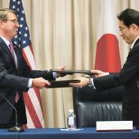U.S. Defense Secretary Ash Carter (left) and Foreign Minister Fumio Kishida exchange signed documents on the 'Agreement to Supplement the Japan-U.S. Status of Forces Agreement (SOFA) on Environmental Stewardship' Monday during a ceremony at the Pentagon. | AP