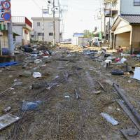 Grass and debris cover a road in Joso, Ibaraki Prefecture, on Sunday morning after floodwaters that ravaged the city receded. | KYODO
