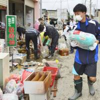 High school students participate in a Volunteer operation to clear a residential area after it was inundated by a major flood in Joso, Ibaraki Prefecture, on Sunday morning. | KYODO