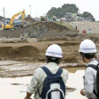 Experts from the Japan Society of Civil Engineers and investigators from the Land, Infrastructure, Transport and Tourism Ministry's Kanto Regional Development Bureau on Sunday morning inspect the area where banks of Kinugawa River collapsed Thursday in Joso, Ibaraki Prefecture. | KYODO