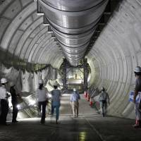 Journalists take part in a walking tour of the underground Furukawa reservoir in Tokyo when it was being built in August 2014. The Tokyo Metropolitan Government is trying to cope with heavy rain by constructing giant reservoirs both above and underground. | BLOOMBERG
