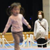 Parents watch their children in a playground set up inside a hall in the city of Fukushima in December 2012. | KYODO