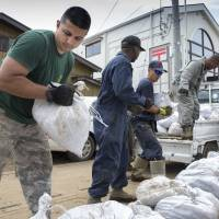 Volunteers from the U.S. military's 374th Civil Engineer Squadron unload bags of mud from a truck in Kanuma, Tochigi Prefecture, on Tuesday. The military said 60 troops and civilians helped shovel flood-related mud from homes in the area. | 374TH AIRLIFT WING
