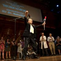 Yoshiro Nakamatsu, a 2005 Ig Nobel award recipient for nutrition, rises from his wheelchair after singing a song he wrote about being diagnosed with a fatal form of cancer at the Ig Nobel Prizes awards ceremony at Harvard University in Cambridge, Massachusetts, Thursday. The annual prizes, meant to entertain and encourage global research and innovation, are awarded by the Annals of Improbable Research as a whimsical counterpart to the Nobel Prizes. Dr. Hajime Kimata of Osaka won the award for his study into how kissing can alleviate allergic symptoms. | REUTERS
