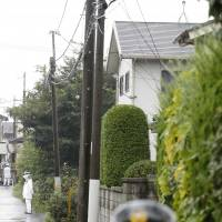 Police officers man the scene at a house on Thursday where a mother and her two daughters were earlier murdered in Kumagaya, Saitama Prefecture. | KYODO