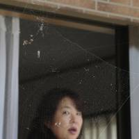 Naoko Kanai watches a spider's web Friday at her house after returning home for the first time in about two months, in Naraha, Fukushima Prefecture. | AP