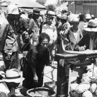 People receive food from the U.S. military in May 1945 at a civilian internment camp in Shimabaru, in what is now Uruma, Okinawa Prefecture. | OKINAWA PREFECTURAL ARCHIVES / KYODO