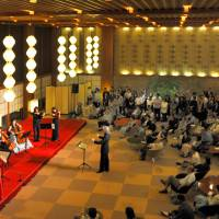 Visitors listen to the last concert held Monday in the main lobby of the Hotel Okura Tokyo. The lobby is famous for hanging lamp shades modeled after ancient gems and are known as Okura lanterns. | YOSHIAKI MIURA