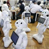 Pepper humanoid robots are shown during a July event in Tokyo. A drunken 60-year-old man was arrested Sunday for allegedly damaging a similar robot in a fit of rage at a SoftBank outlet, police said. | KYODO