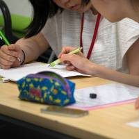 A university student volunteer teaches math to a junior high school student at the Tadazemi free cram school in Tokyo. | BLOOMBERG
