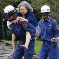 An elderly woman is carried by a firefighter after being rescued Friday by a helicopter in Joso, Ibaraki Prefecture. Search and rescue of residents resumed Friday, a day after raging floodwaters broke through an embankment and swamped the city, washing away houses and forcing dozens of people to rooftops.  | AP