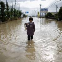 A local resident wades through a residential area flooded by the Kinugawa River, in Joso, Ibaraki Prefecture.   REUTERS