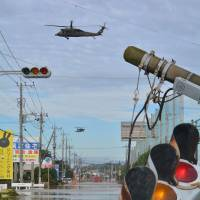 A military helicopter flies over a flooded street on Friday during a rescue mission in the city of Joso in Ibaraki Prefecture. | AFP-JIJI