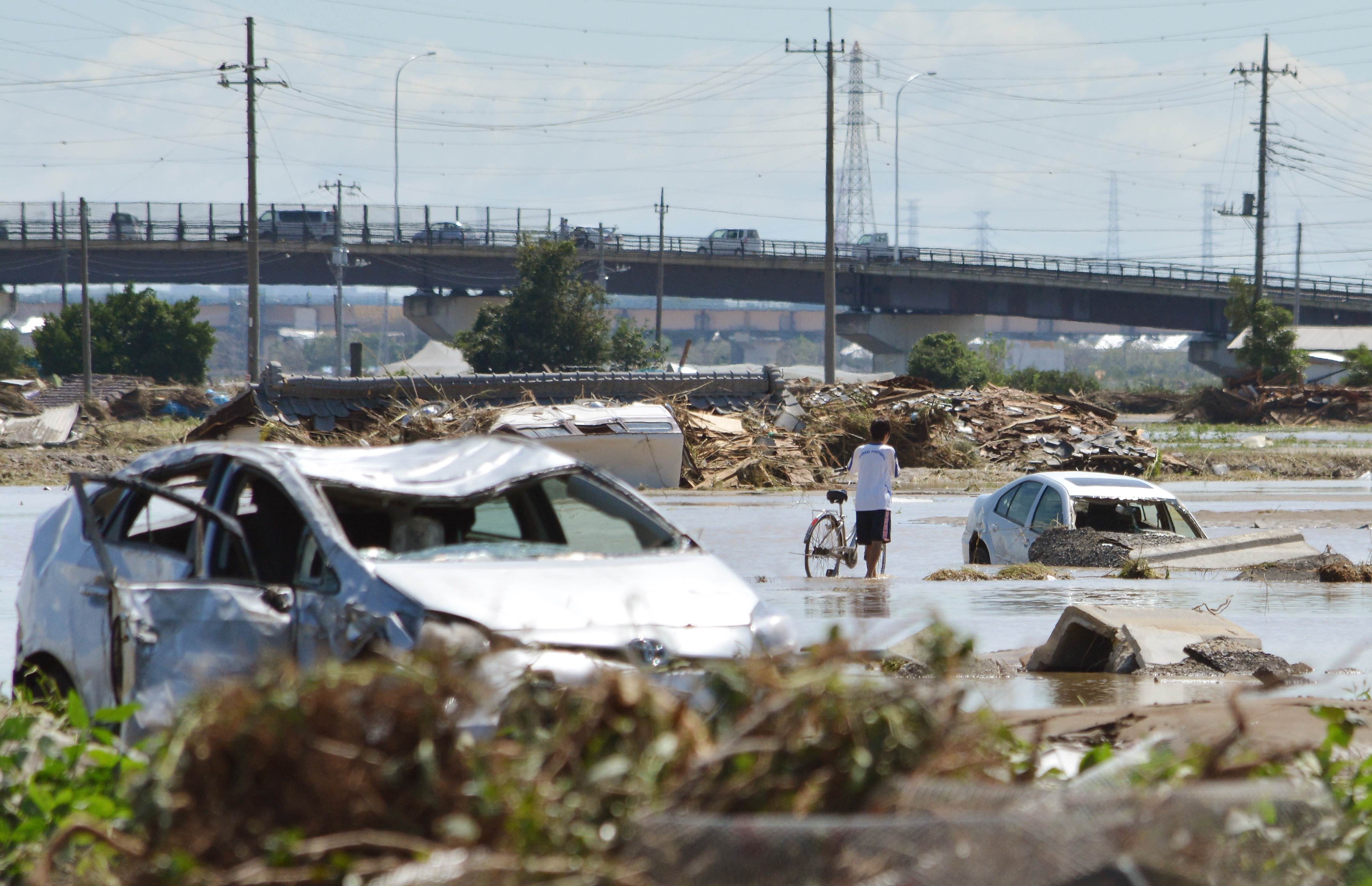 A man pushes his bicycle past stranded vehicles in muddy water in Joso, Ibaraki Prefecture on Friday. Thousands of rescuers arrived Friday to help evacuate hundreds of trapped residents and search for people missing after torrential rains triggered massive flooding.    AFP-JIJI