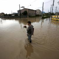 A woman holding her pet dog wades through a residential area flooded by the Kinugawa River, caused by typhoon Etau, in Joso, Ibaraki prefecture on Thursday. | REUTERS