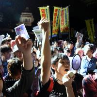 Demonstrators shout slogans to protest two disputed security bills during a rally in front of the Diet on Thursday evening. | SATOKO KAWASAKI