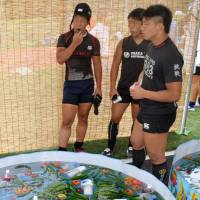 High school rugby players eat vegetables provided by local residents at the Gose rugby festival in Gose, Nara Prefecture, on July 21. | KYODO