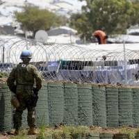 A member of the Ground Self-Defense Force guards a fence at a refugee camp in Juba, the capital of South Sudan, on July 24 as part of a U.N. peacekeeping operation.   KYODO