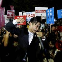 Aki Okuda, a founding member of the student protest group SEALDs, shouts slogans during a rally in front of the Diet on Tuesday. | REUTERS