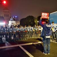 A demonstrator faces off with police outside the Diet building in Tokyo early Saturday while holding up a sign with an anti-war slogan. | KYODO