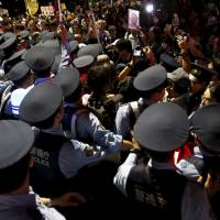 Police officers detain protesters taking part in a rally against the government's security bills in front of the Diet on Tuesday. More protests will likely continue later in the week as the ruling bloc gears up for the passage of the bills. | REUTERS