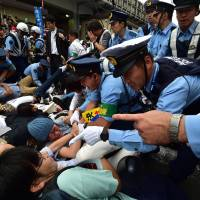 Police attempt to remove demonstrators lying on the ground to block a vehicle transporting members of the Upper House's committee on the security bills outside the venue for a public hearing on the legislation in Yokohama on Wednesday. | AFP-JIJI