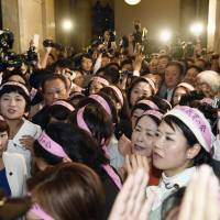Opposition female lawmakers wearing pink headbands cry foul over government-sponsored security legislation Wednesday evening in the Diet, where they delayed the start of the Upper House special committee on the bills. | KYODO