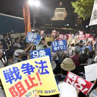Protesters holding placards walk toward the Diet on Friday evening as the passage of Prime Minister Shinzo Abe's contested security bills loomed. | KYODO