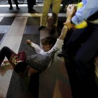 A protester falls as a police officer holds his arm during a rally against Japan's Prime Minister Shinzo Abe's security bill and his administration in front of the parliament in Tokyo on Tuesday. Three protestors were eventually arrested. | REUTERS