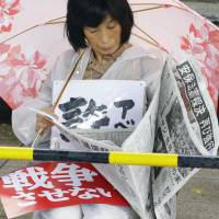 A protester reads a newspaper in the rain outside the Diet on Friday. The red placard says '(We) won't let (the nation) go to war.' The white one says 'Abe.' The newspaper headline set in black reads: 'Vote on security bills bulldozed again.' | KYODO