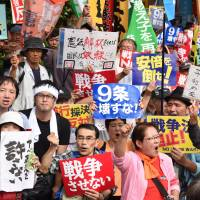 Protesters at the Diet shout slogans Friday opposing Prime Minister Shinzo Abe's attempt to give the Self-Defense Forces a bigger role overseas. Visible are messages such as 'Don't destroy Article 9,' 'If we change the interpretation of the Constitution, people can be made into slaves' and 'We don't tolerate Abe politics.' | KYODO