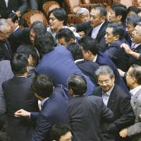 Opposition lawmakers rush Yoshitada Konoike (left), chairman of the Upper House special committee on the security bills, as the session turns chaotic Thursday afternoon.   KYODO