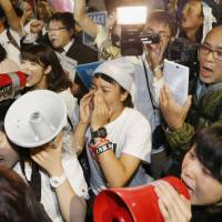 Protesters outside the Diet early Saturday denounce moves to pass the security bills. | KYODO