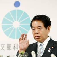 Sports minister Hakubun Shimomura addresses reporters Friday after offering to resign over the scrapping of the costly stadium construction plan. | KYODO