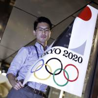 A poster bearing the scrapped Tokyo 2020 Olympics logo is removed during an event staged for photographers at the Tokyo Metropolitan Government building on Tuesday. | AP