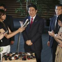 Prime Minister Shinzo Abe tells reporters in Tokyo on July 17 that plans for the main stadium of the 2020 Olympics would be scrapped and the project redrawn from scratch. | AP