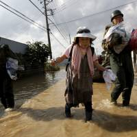 Yoshiko Nakamura, 66, is escorted Saturday by Self-Defense Force's soldiers as she leaves her home in Joso, Ibaraki Prefecture, where the torrential rains of Typhoon Etau caused major flooding last week.  | REUTERS