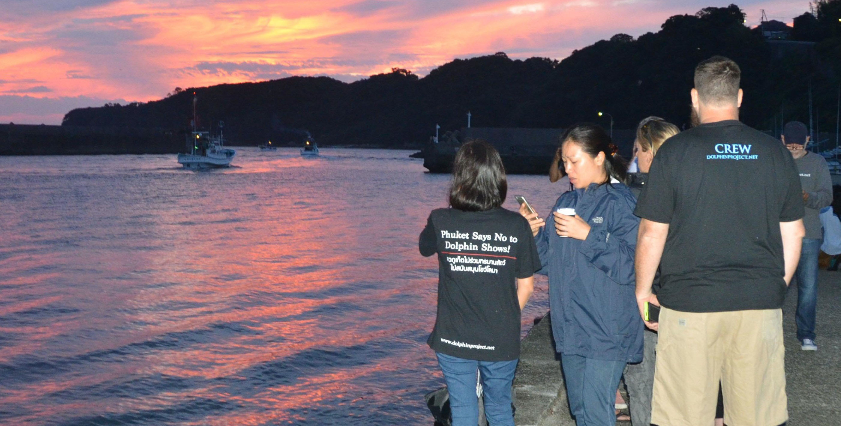 Members of an animal conservation group watch dolphin hunters leaving the port of Taiji, Wakayama Prefecture, early Thursday for the season's first dolphin drive hunt.   KYODO